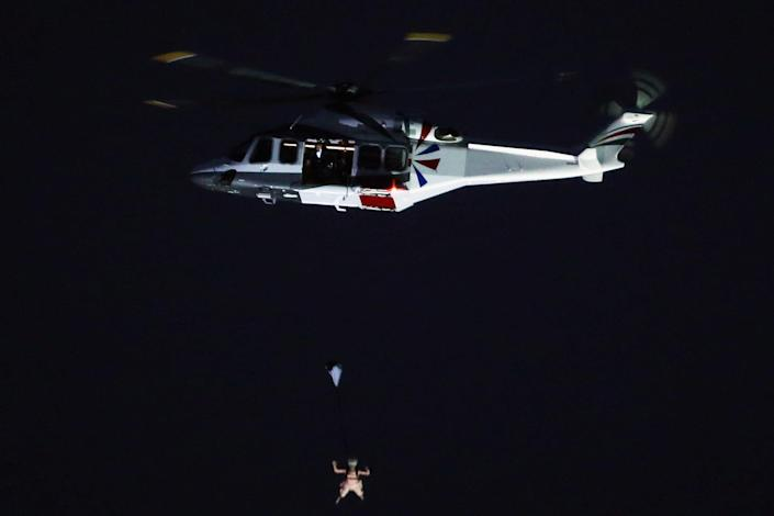 A person dressed as Queen Elizabeth parachutes into the Olympics stadium (Getty Images)