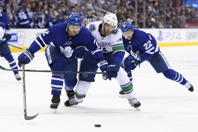 Toronto Maple Leafs defenseman Ron Hainsey (2) and Vancouver Canucks center Brandon Sutter (20) battle for the puck during the second period of an NHL hockey game, in Toronto, Saturday, Jan. 5, 2019. (Nathan Denette/The Canadian Press via AP)