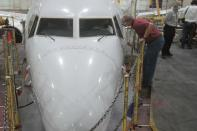 A worker speaks to a man who loads new software into the Boeing 737 Max airplane in a maintenance hanger in Tulsa