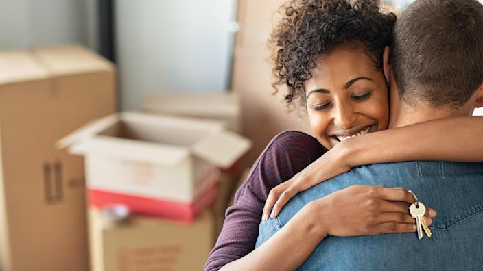 Young african woman holding home keys while hugging boyfriend in their new apartment after buying real estate.