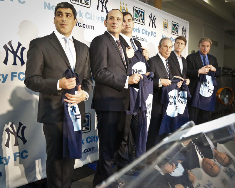 Former U.S. Soccer national team captain Claudio Reyna, left, MLS Commissioner Don Garber, second from left, CEO of Manchester City Football Club Ferran Soriano, third from left, New York City Mayor Michael Bloomberg, third from right, New York Yankees general manager Hal Steinbrenner, second from right, and Yankees president Randy Levine, gather for a photo-op after a press conference on Wednesday, May 22, 2013 in New York.  Reyna was named director of football for the New York City Football Club, the 20th expansion team for Major League Soccer acquired through a partnership between MCFC and the New York Yankees.  (AP Photo/Bebeto Matthews)