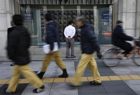 A man looks at a stock quotation board as passers-by walk past outside a brokerage in Tokyo January 28, 2014. REUTERS/Toru Hanai