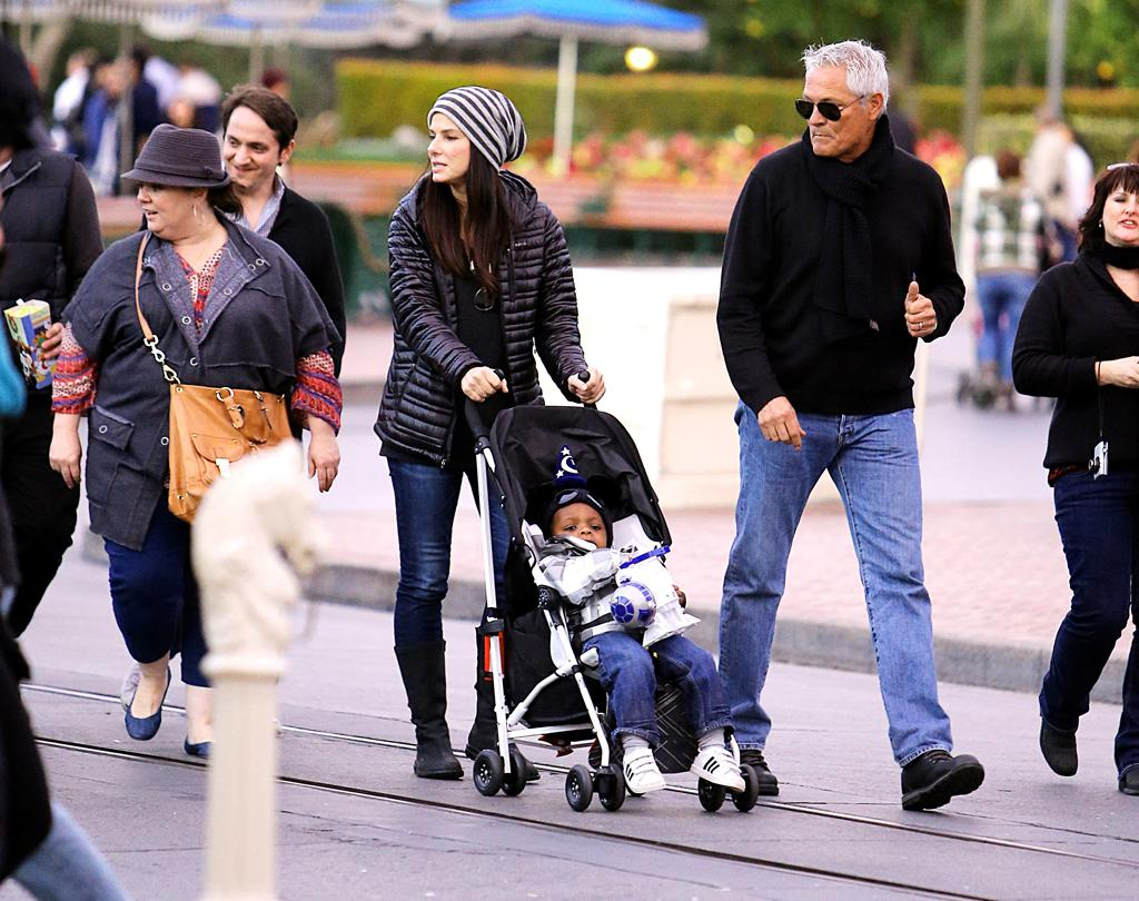 Sandra Bullock was spotted spending the day at the Disneyland resort in Anaheim, CA with actress Melissa McCarthy. The two actresses also brought along their families to Disneyland and California Adventure. The gal pals were joined by Melissa's husband Ben Falcone and their two daughters, Sandra brought along her son Louis Bardo and her gray haired bodyguard. They enjoyed their day with the help of a VIP guide that got them passed all the long lines. Sandra was seen buying baby Louis some Mickey ears before putting him in his stroller where he was seen eating popcorn out of an R2D2 bowl. The two mothers were seen racing their kids in their strollers while making their way out of the park. Before ending their night, Sandra and Melissa were seen embracing each other with a friendly hug while walking to their cars. Pictured: Sandra Bullock, Louis Bardo, Melissa McCarthy, Ben Falcone Ref: SPL471226 141212 Picture by: Sharpshooter Images /Splash Splash News and Pictures Los Angeles: 310-821-2666 New