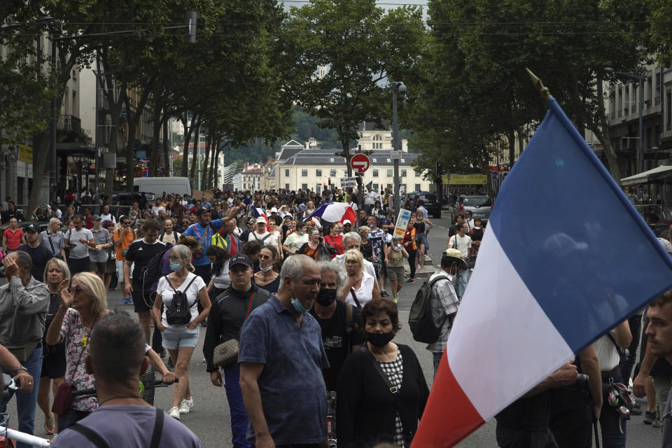 Protestors march waving French flags during a demonstration in Lyon, central France, Saturday, July 31, 2021. Demonstrators gathered in several cities in France on Saturday to protest against the COVID-19 pass, which grants vaccinated individuals greater ease of access to venues. (AP Photo/Laurent Cipriani)