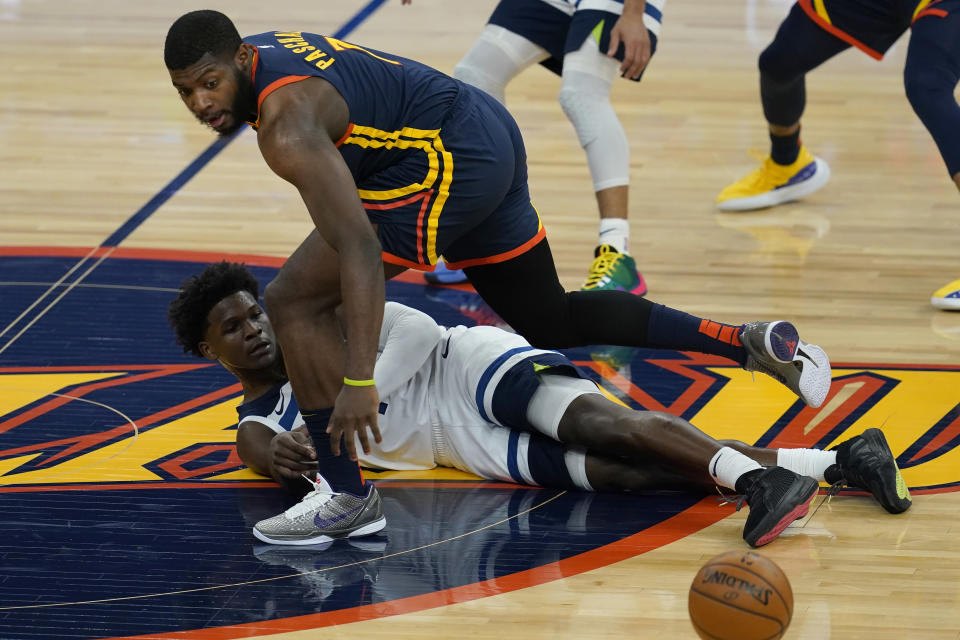 Minnesota Timberwolves guard Anthony Edwards, bottom, passes the ball under Golden State Warriors forward Eric Paschall during the first half of an NBA basketball game in San Francisco, Wednesday, Jan. 27, 2021. (AP Photo/Jeff Chiu)