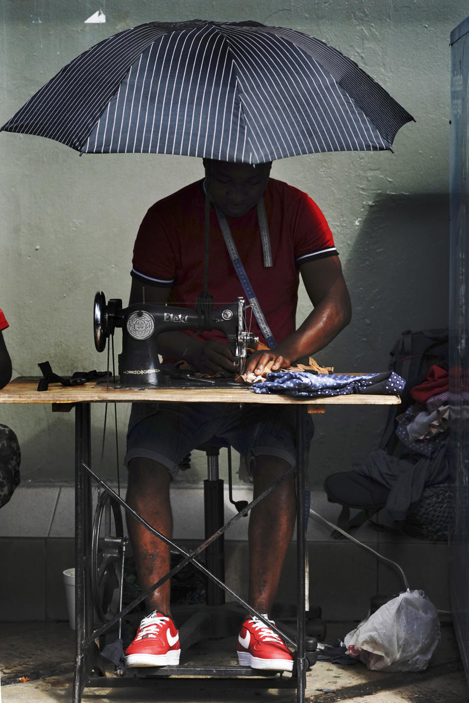 FILE - In this Sept. 3, 2021 file photo, a Haitian migrant operates a sewing machine at a market in Tapachula, Mexico. Thousands of mostly Haitian migrants have been stuck in the southern city of Tapachula, many waiting here for months and some up to a year for asylum requests to be processed. (AP Photo/Marco Ugarte, File)