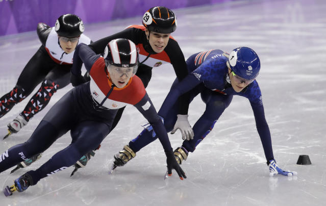 Elise Christie, right, of Britain stumbles during a women's 1000 meters short track speedskating heat