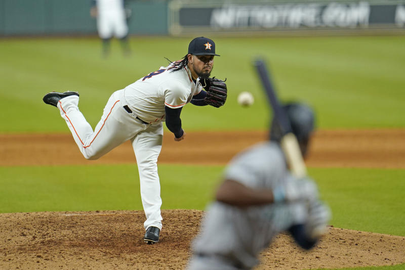 Houston Astros relief pitcher Roberto Osuna, left, throws to Seattle Mariners' Kyle Lewis during the ninth inning of a baseball game Monday, July 27, 2020, in Houston. The Astros won 8-5. (AP Photo/David J. Phillip)