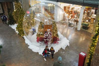 Father Frost looks through decorated 10-foot snow globe at Trolley Square in Salt Lake City on Dec. 10, 2020. In this socially distant holiday season, Santa Claus is still coming to towns (and shopping malls) across America but with a few 2020 rules in effect. (AP Photo/Rick Bowmer)