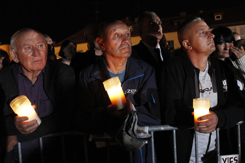 Spectators hold candles in their hands at the memorial service during ceremony marking 80th anniversary of World War II start at the exact place and time when Nazi Germany dropped its first bombs in the war, in Wielun, Poland, Sunday, Sept. 1, 2019. Observances in Warsaw will be attended by U.S. Vice President Mike Pence, in place of invited President Donald Trump.(AP Photo/Czarek Sokolowski)
