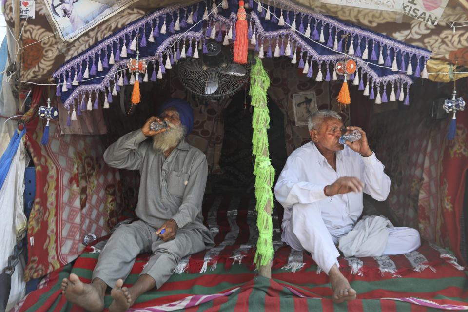 Indian farmers drink water sitting at the back of their tractor trolly as they camp at Singhu, along the Delhi-Haryana border, Friday, March 5, 2021. Saturday marks 100 days of the ongoing farmer protests against the contentious new agricultural reform laws which have led tens of thousands of farmers to blockade key highways leading to the capital. Multiple rounds of talks have failed to produce any breakthrough on the farmers' key demand to revoke the legislation. (AP Photo/Manish Swarup)