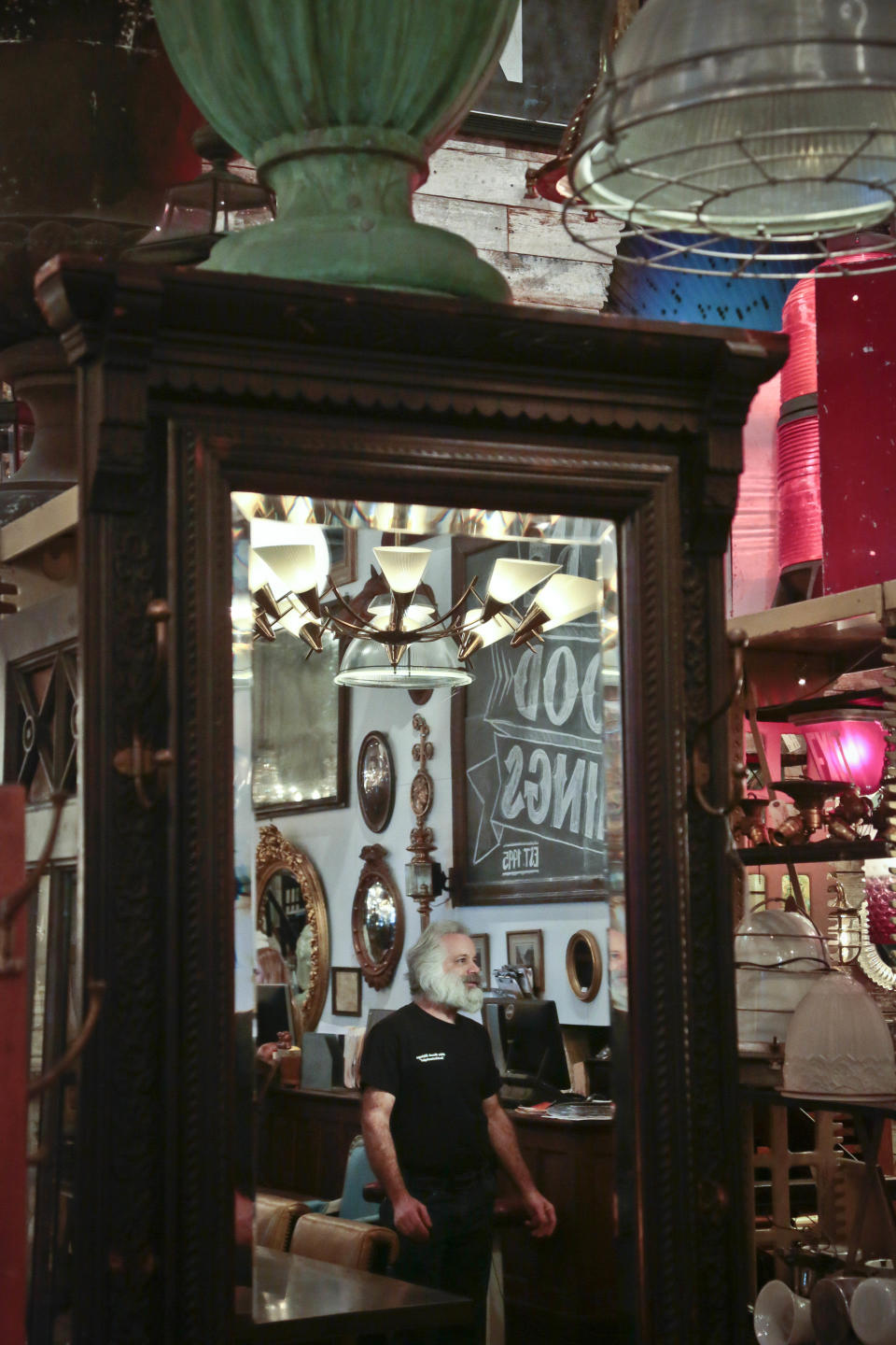 In this Nov. 22, 2013 photo, store manager Jim Digiacoma is reflected in a mirror at the Olde Good Things antique store in New York. The store's Christian missionary owners offer their well-heeled customers a heart-warming story: Part of the proceeds pay for the group's orphanage in Haiti, one of the poorest countries in the world. What they don't say is that even though they claim in IRS filings to be spending around $2.5 million annually, the home for boys and girls was so dirty and overcrowded during recent inspections that the government said it shouldn't remain open. (AP Photo/Bebeto Matthews)