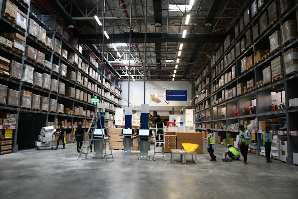 "Indian workers give final touches at the warehouse area of the new IKEA store in Hyderabad on August 8, 2018. - Ikea's boss promised on August 8 to meet the ""needs, frustrations and dreams"" of local consumers with the Swedish firm's first Indian store, its second attempt to break into a vast but difficult market. (Photo by NOAH SEELAM / AFP) (Photo credit should read NOAH SEELAM/AFP via Getty Images)"