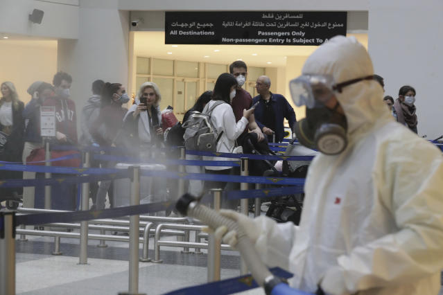Passengers line up as workers wearing protective gear spray disinfectant as a precaution against the coronavirus outbreak, in the departure terminal at the Rafik Hariri International Airport, in Beirut, Lebanon, Thursday, March 5, 2020. (AP Photo/Hassan Ammar)