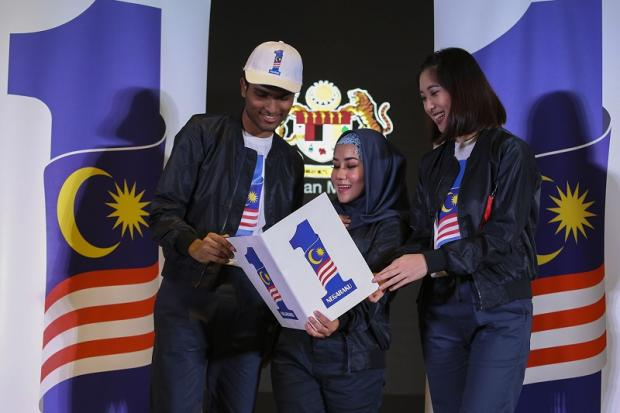 (From left) Theeban Mahendran, Siti Hasreena Rosli and Yvonne Lee Hui Lee of the Lim Kok Wing Choir looking at the new 1Malaysia Negaraku logo during the launch event in Putrajaya August 23, 2017.