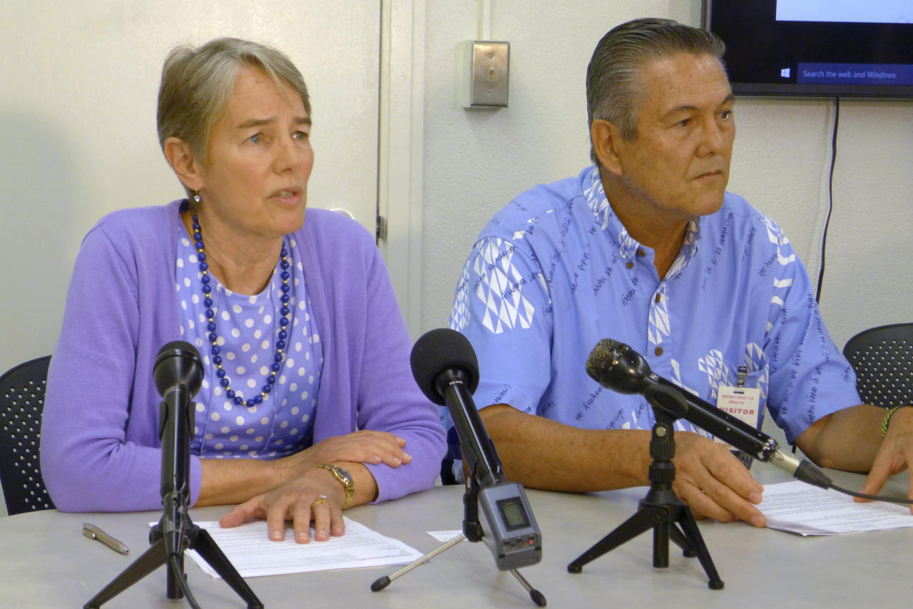 File - In this April 19, 2017, file photo, Hawaii Health Director Virginia Pressler, left, and Hawaii Tourism Authority CEO George Szigeti, right, talk to members of the media about new cases of rat lungworm disease in Honolulu. A California couple on their honeymoon and two people who drank a homemade beverage are among the rising number of victims in Hawaii falling ill with a potentially deadly brain parasite. After the newlyweds' plight with rat lungworm disease recently got attention online, the couple and some experts accused Hawaii of failing to adequately warn tourists and residents of the danger. Tourism officials are assuring visitors that the disease is rare and there's no need to cancel vacation plans. (AP Photo/Cathy Bussewitz, File)