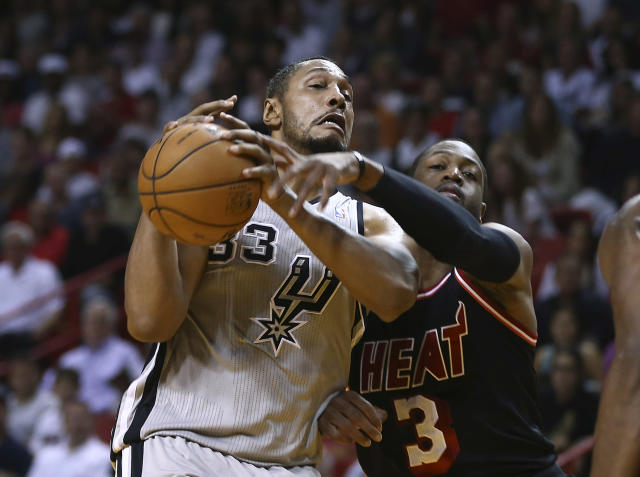 Miami Heat's Dwyane Wade (3) knocks the ball from San Antonio Spurs' Borks Diaw (33) hands during the first half of a NBA basketball game in Miami, Sunday, Jan. 26, 2014. (AP Photo/J Pat Carter)