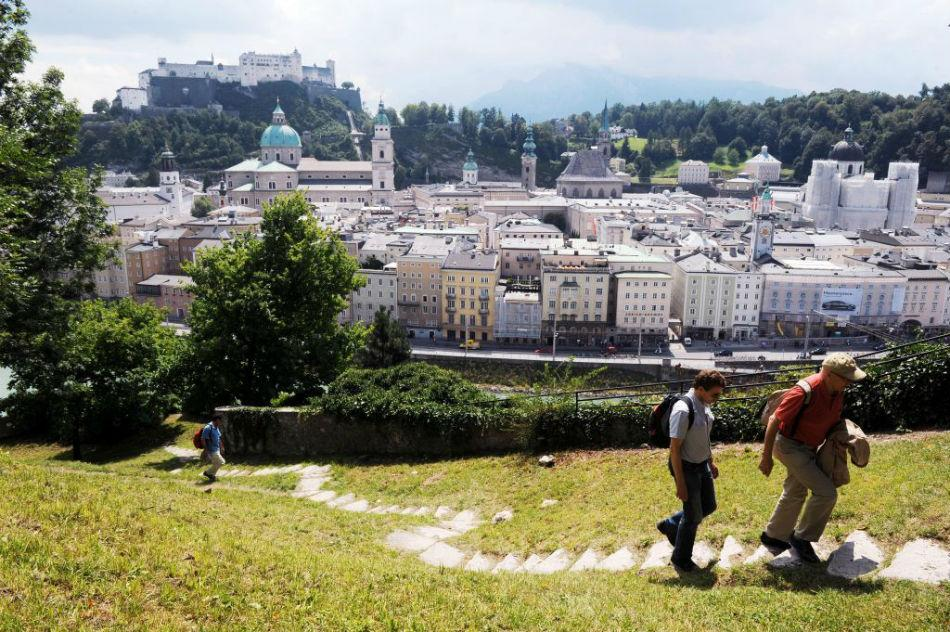Hikers on capuchin hill with Fortress Hohensalzburg and the old town center in the background can be seen.