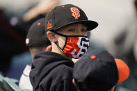 A young baseball fan wears a face mask while watching a spring baseball game between the San Francisco Giants and the Los Angeles Angels in Scottsdale, Ariz., Sunday, Feb. 28, 2021. (AP Photo/Jae C. Hong)