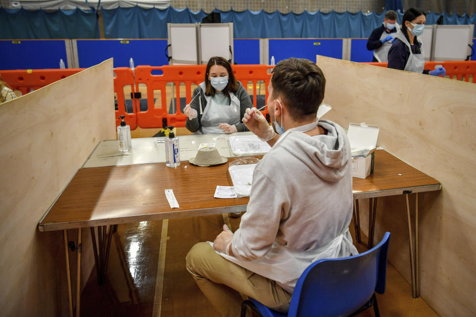 "Testing staff members complete lateral flow test swabs, mandatory before opening to the public, at Rhydycar leisure centre in Merthyr Tydfil, Wales, Saturday, Nov. 21, 2020. where mass coronavirus testing begins following a two-week ""firebreak"" lockdown. (Ben Birchall/PA via AP)"