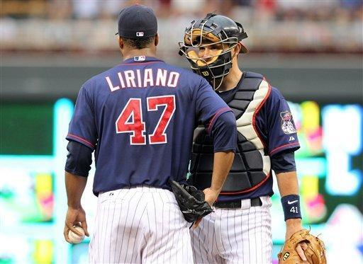CORRECTS TO CATCHER DREW BUTERA NOT JOE MAUER - Minnesota Twins starting pitcher Francisco Liriano, left, talks with Twins catcher Drew Butera, right, between pitches against the Baltimore Orioles during the second inning of a baseball game on Wednesday, July 18, 2012, in Minneapolis. (AP Photo/Genevieve Ross)