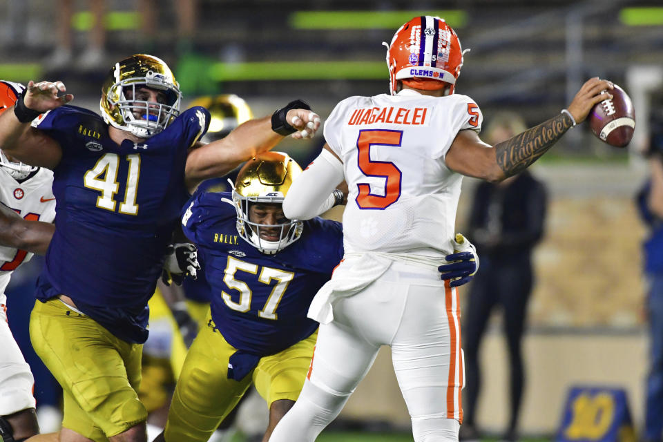 Notre Dame defensive linemen Kurt Hinish (41) and Jayson Ademilola (57) pressure Clemson quarterback D.J. Uiagalelei (5) during the third quarter of an NCAA college football game Saturday, Nov. 7, 2020, in South Bend, Ind. (Matt Cashore/Pool Photo via AP)