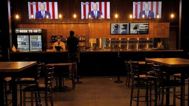 PHOTO: Televisions at Good City Brewing show footage of Democratic presidential nominee Joe Biden during the Democratic National Convention in Milwaukee, Aug. 19, 2020. (Brian Snyder/Reuters)