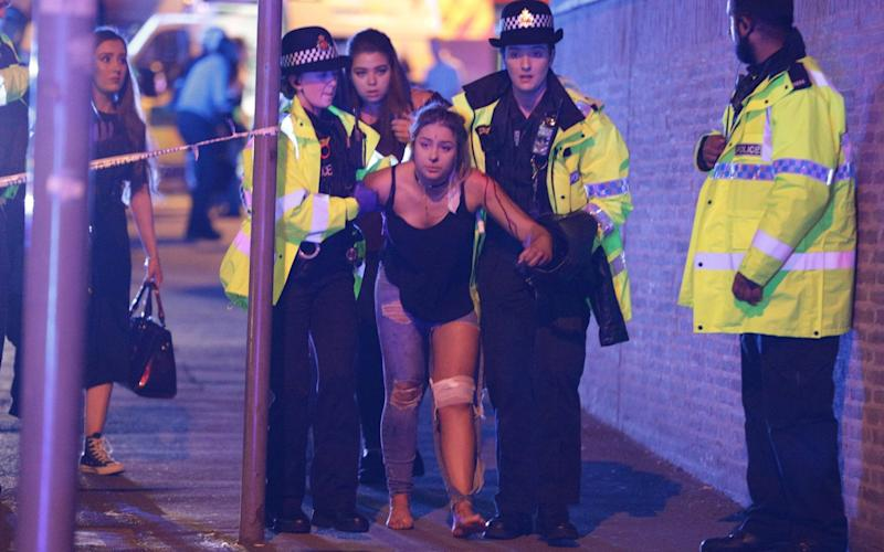 An injured woman is helped by police after the blast - Credit: Joel Goodman/LNP