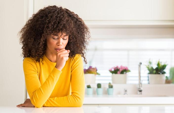 woman wearing yellow sweater at kitchen feeling unwell and coughing as symptom for cold or bronchitis