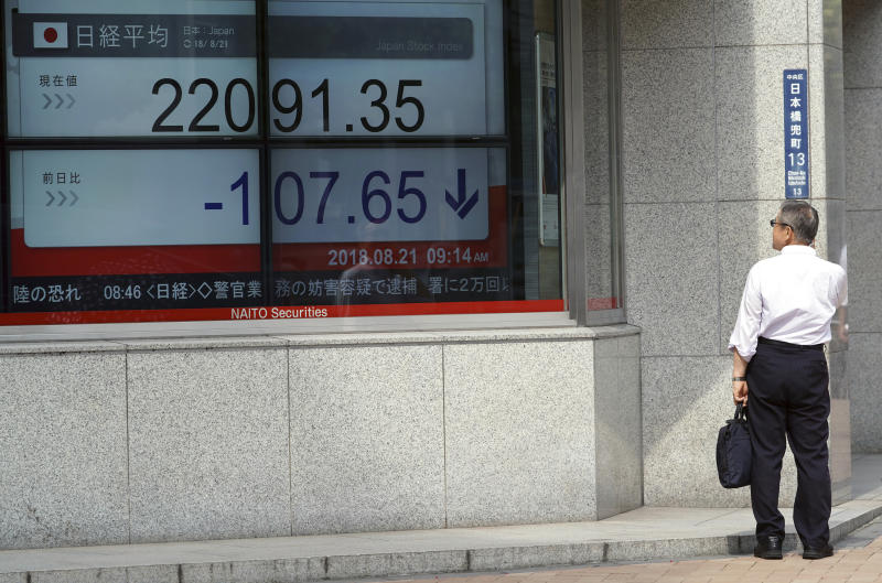 A man looks at an electronic stock board showing Japan's Nikkei 225 index at a securities firm Tuesday, Aug. 21, 2018, in Tokyo. Asian shares are mixed amid doubts on the prospects for resolving the trade dispute between the U.S. and China. (AP Photo/Eugene Hoshiko)