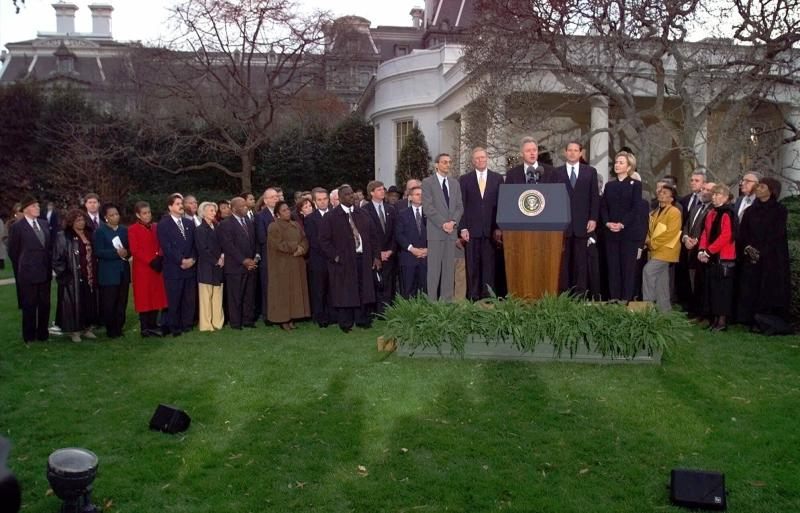 FILE - In this Dec. 19, 1998, file photo, then-President Bill Clinton is joined by Democratic lawmakers and aides outside the Oval Office of the White House in Washington, after the House of Representatives voted to impeach the president. Twenty-one years ago this Thursday, a Republican-led House voted to impeach then-President Bill Clinton. While that battle was bitterly partisan, it was blurrier than the clean, near party-line votes expected this week when the chamber _ now run by Democrats _ is poised to impeach President Donald Trump. (AP Photo/Doug Mills, File)