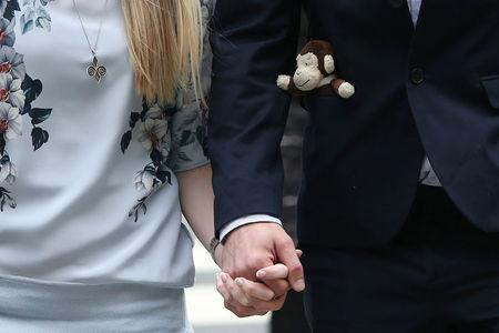 The father of critically ill baby Charlie Gard carries a toy monkey in his pocket as he and Connie Yates, Charlie Gards mother, arrive at the High Court in London