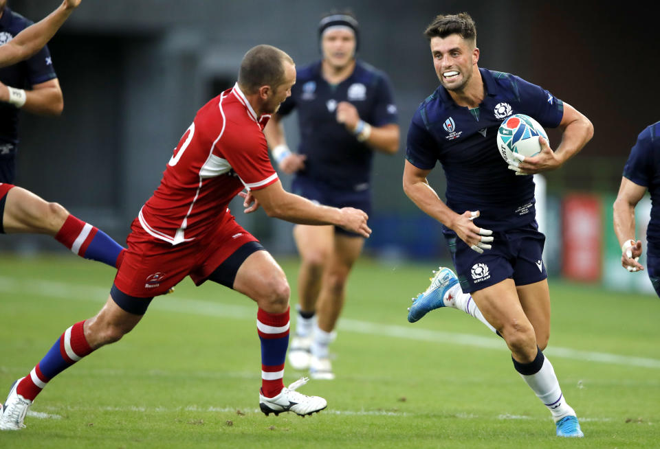 Scotland's Adam Hastings rans at Russia's Ramil Gaisin, left, during the Rugby World Cup Pool A game at Shizuoka Stadium Ecopa between Scotland and Russia in Shizuoka, Japan, Wednesday, Oct. 9, 2019. (AP Photo/Christophe Ena)
