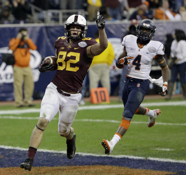 Minnesota wide receiver Drew Wolitarsky (82) celebrates after scoring a touchdown as Syracuse cornerback Brandon Reddish (4) defends during the second half of the Texas Bowl NCAA college football game on Friday, Dec. 27, 2013, in Houston. Syracuse won 21-17. (AP Photo/David J. Phillip)