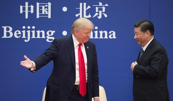 US President Donald Trump gestures to China's President Xi Jinping during a business leaders event at the Great Hall of the People in Beijing on November 8, 2017. Photo: AFP