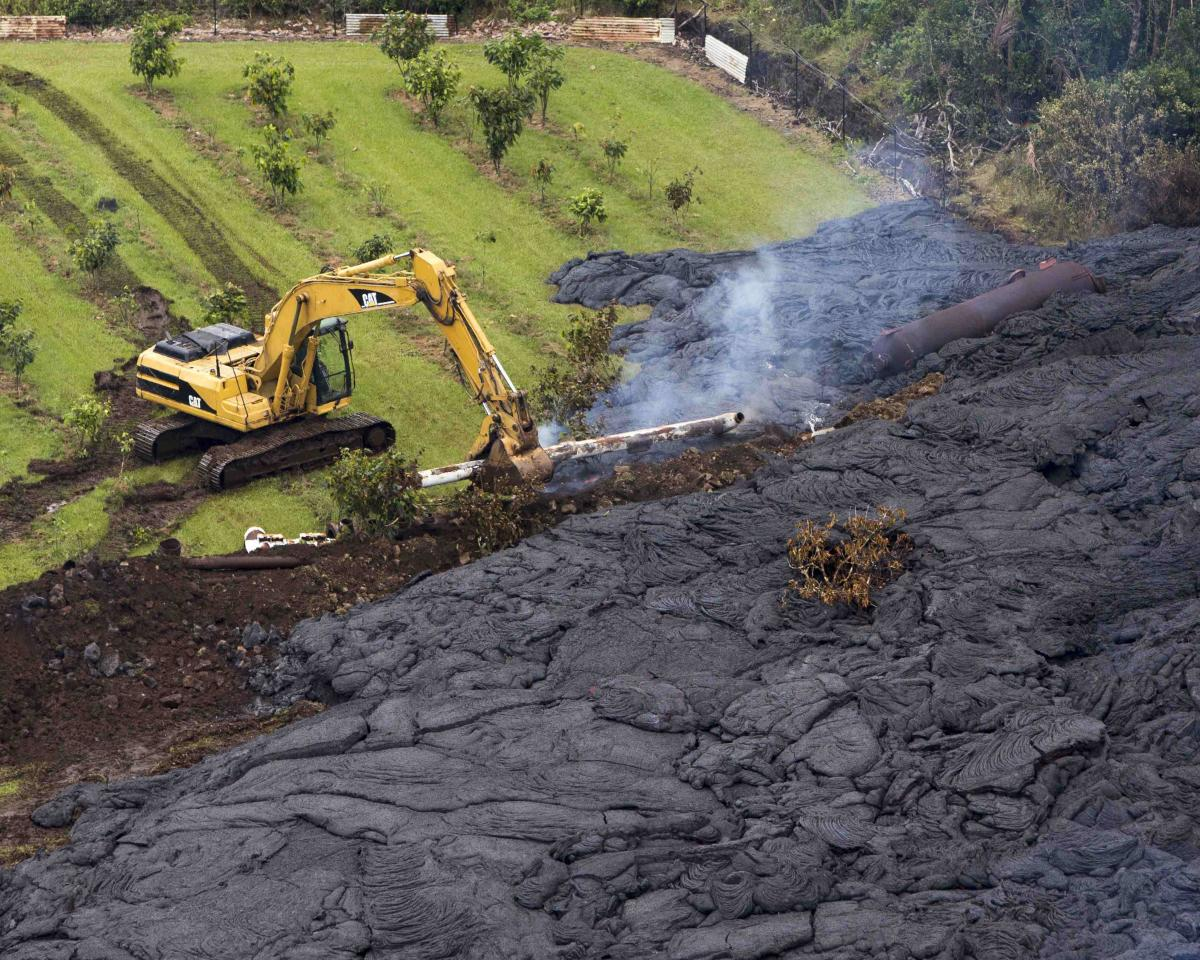 A construction crew tries to contain the lava flow from Mount Kilauea in Pahoa, Hawaii October 29, 2014. The slow-moving river of molten lava from the erupting Kilauea volcano crept over residential and farm property on Hawaii's Big Island on Wednesday after incinerating an outbuilding as it threatened dozens of homes at the edge of the former plantation town. REUTERS/Marco Garcia (UNITED STATES - Tags: DISASTER ENVIRONMENT TPX IMAGES OF THE DAY)