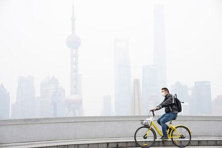 A man wearing a face mask rides a bicycle on a bridge in front of the financial district of Pudong covered in smog during a polluted day in Shanghai