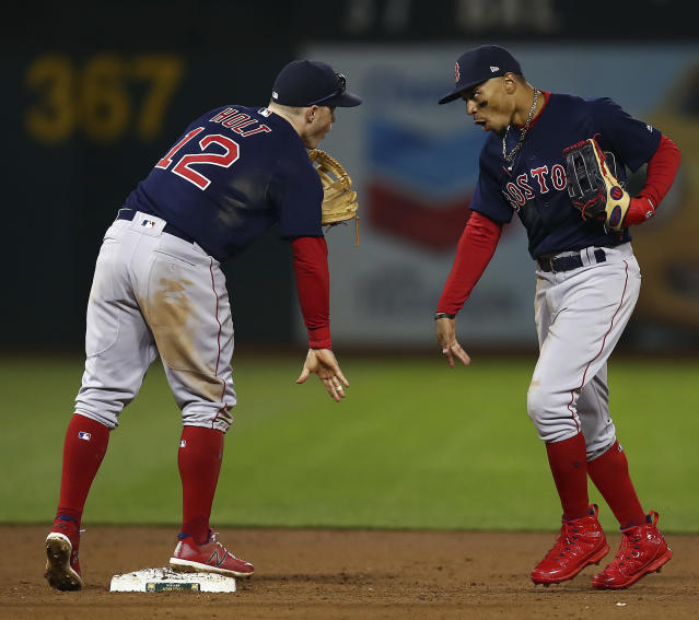 Boston Red Sox's Brock Holt (12) celebrates the 7-3 win over the Oakland Athletics with Mookie Betts at the end of a baseball game, Friday, April 20, 2018, in Oakland, Calif. (AP Photo/Ben Margot)