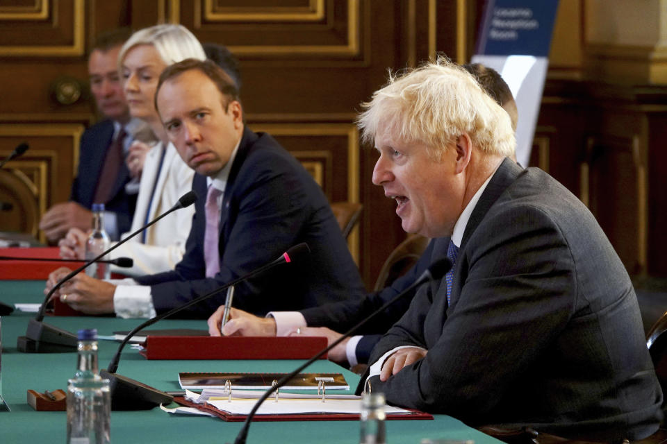 Britain's Prime Minister Boris Johnson, right, chairs a socially distanced government Cabinet meeting at the Foreign and Commonwealth Office (FCO) in London, Tuesday Sept. 15, 2020. Health Secretary Mat Hancock, centre, and International Trade Secretary Liz Truss, 2nd left. (Jonathan Buckmaster/Pool via AP)