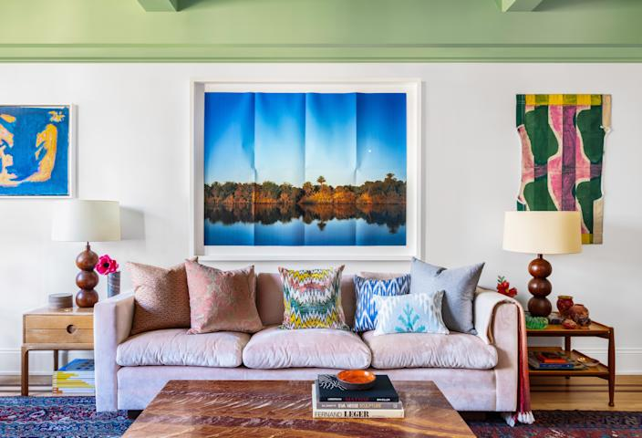 "<div class=""caption""> ""The living room overlooks a garden, which is really pretty in the summertime,"" Joey says. ""The green ceiling <a href=""https://www.architecturaldigest.com/story/painting-tips-paint-color-ideas?mbid=synd_yahoo_rss"" rel=""nofollow noopener"" target=""_blank"" data-ylk=""slk:paint"" class=""link rapid-noclick-resp"">paint</a> was meant to complement all that greenery outside. I didn't tell my partner that I was doing it at the time, because I didn't think he'd go for it, but he loves it."" </div>"