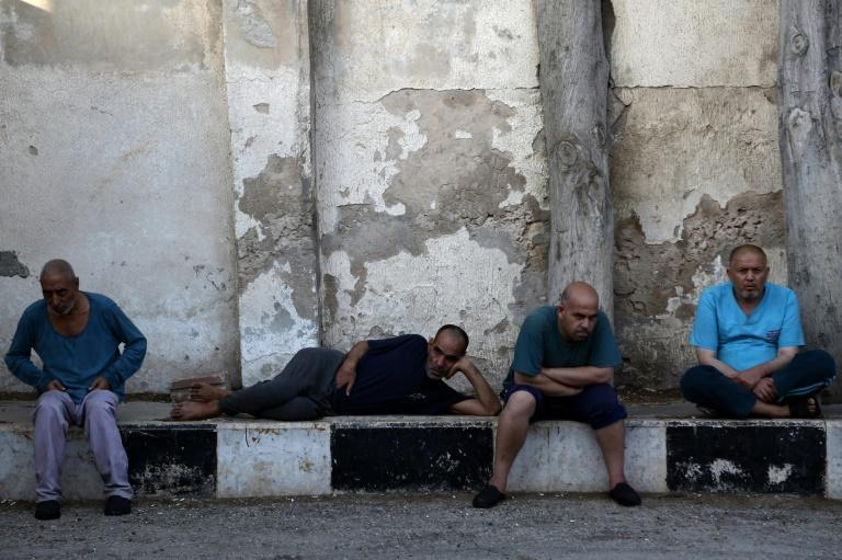 Syrian patients sit in a yard at the mental health clinic, which serves people with mental health issues caused by Syria's devastating war, on July 6, 2017