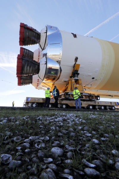 Security and safety personnel walk with the core stage of NASA's Space Launch System rocket, that will be used for the Artemis 1 Mission, as it is moved to the Pegasus barge, at the NASA Michoud Assembly Facility where it was built, in New Orleans, Wednesday, Jan. 8, 2020. It will be transported to NASA's Stennis Space Center in Mississippi for its green run test. (AP Photo/Gerald Herbert)
