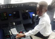 "Ugandan ""Captain"" Graham Shema, is seen inside the cockpit of a Bombardier CRJ900 aircraft at the Entebbe International Airport, in Entebbe"