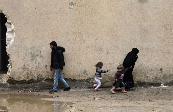 Internally displaced people walk at an empty school and university compound used as shelter, in Azaz