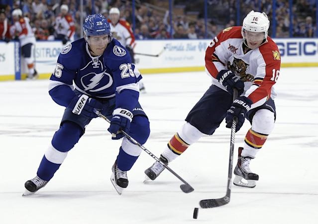Florida Panthers center Shawn Matthias (18) and Tampa Bay Lightning defenseman Matt Carle (25) reach for the puck during the first period of an NHL hockey game Thursday, Oct. 10, 2013, in Tampa, Fla. (AP Photo/Chris O'Meara)