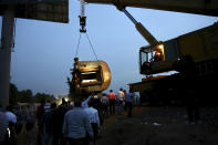 A crane is used to lift a part of a passenger train that derailed injuring around 100 people, near Banha, Qalyubia province, Egypt, Sunday, April 18, 2021. At least eight train wagons ran off the railway, the provincial governor's office said in a statement. (AP Photo/Fadel Dawood)