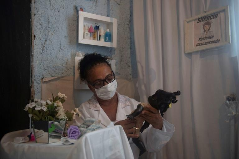 Suelen da Silva lost her job at the start of the coronavirus pandemic but is making ends meet with her 'doll hospital' at her home in Niteroi outside Rio de Janeiro