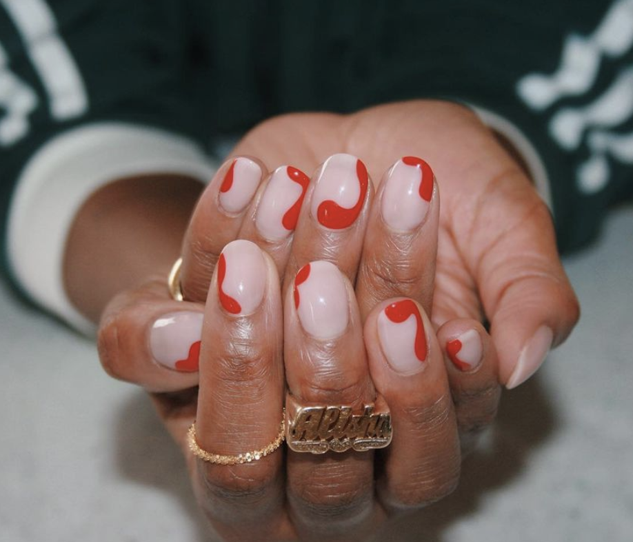 <p>For an abstract and understated manicure, try red swirls in all shapes and sizes around a pale pink nail.</p>
