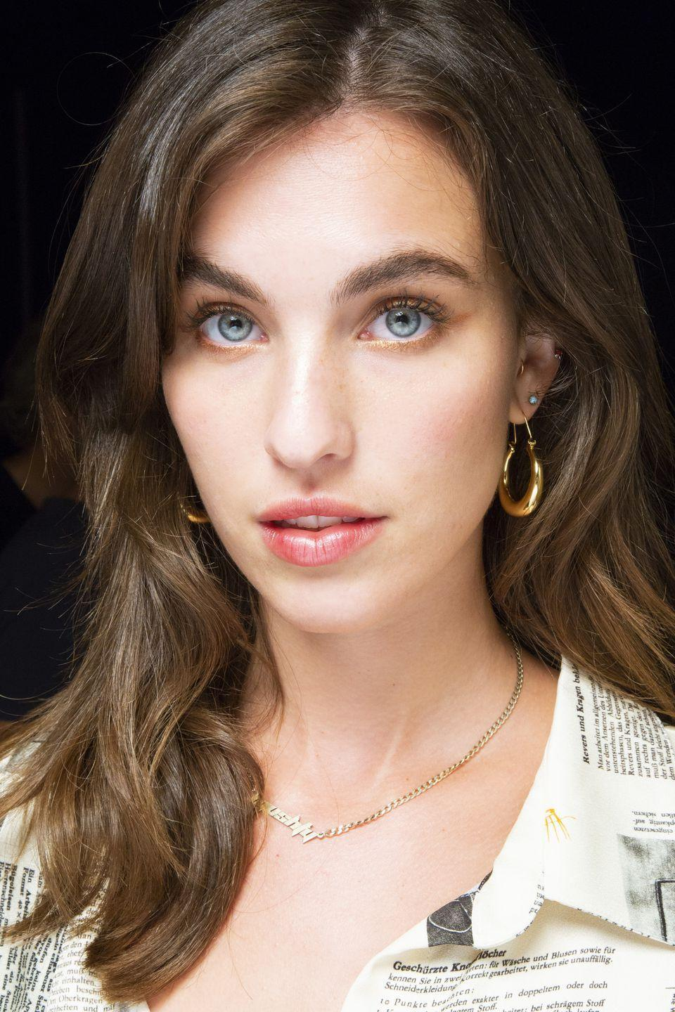<p>Models at Monse wore subtle gold eyeshadow traced along their top and bottom lashlines and flicked out at the end like eyeliner with a stained pink lip.</p>