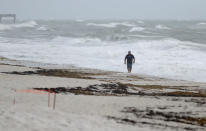 A beach goer walks along the shore as waves churned up by Tropical Storm Isaias crash near Jaycee Beach Park, Sunday, Aug. 2, 2020, in Vero Beach, Fla. Isaias weakened from a hurricane to a tropical storm late Saturday afternoon, but was still expected to bring heavy rain and flooding as it barrels toward Florida. (AP Photo/Wilfredo Lee)